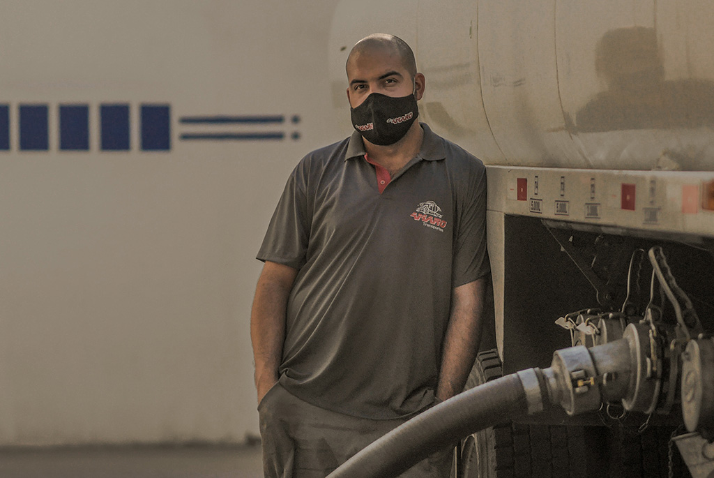 man leaning on truck with mask on
