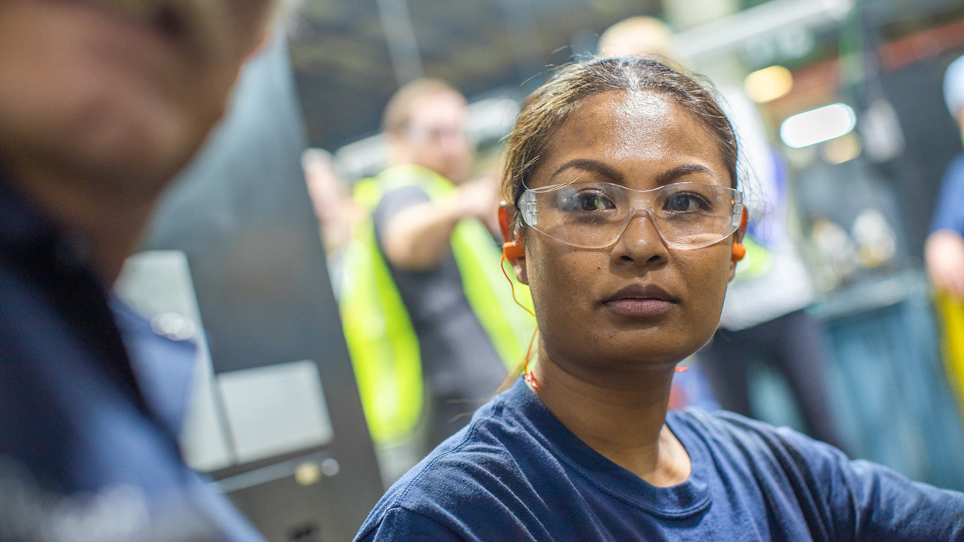 Woman at a manufacturing facility being taught how to use equipment