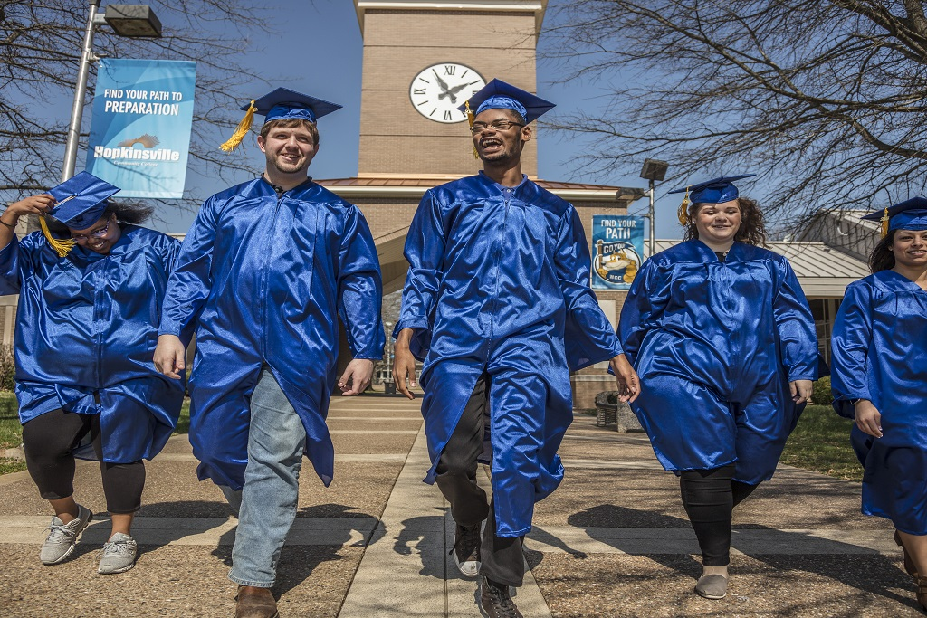 graduates walking on campus in caps and gowns