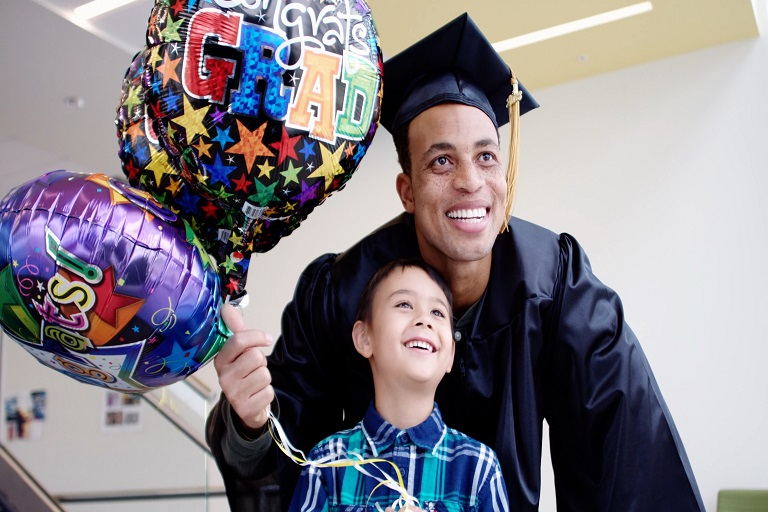 man in cap and gown posing with a kid