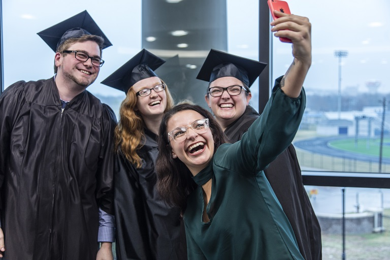 four students at graduation taking a selfie