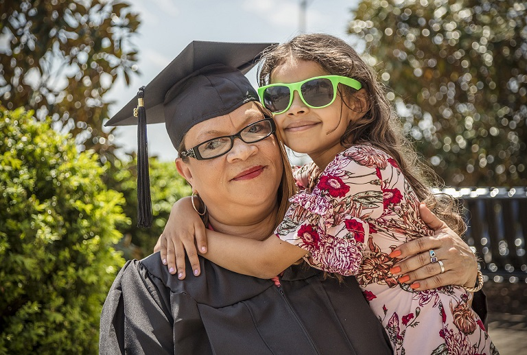 Mother in cap and gown holding her daughter