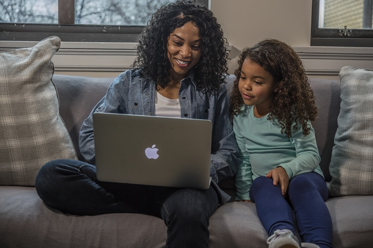 mom on couch on laptop with daughter
