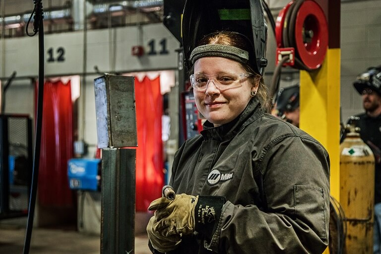 woman in welding uniform posing for camera