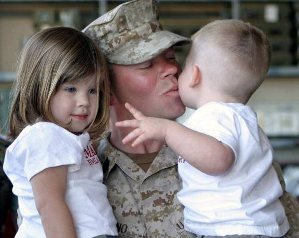 Service member holding small children